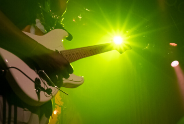 guitar with a green light behind it